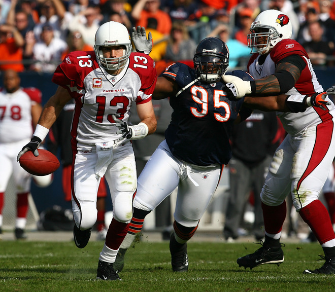 Kurt Warner of  the  Arizona  Cardinals  makes  his way out of the  pocket as he's  pursued  by the   Bears  Anthony  Adams .  Also  assisting  on  the  play  for   the  Cardinals  is   Reggie  Wells  seen to the  left  of  Adams.   picture  appears  courtesy  of  getty  images/  Johnathan  Daniel  .............