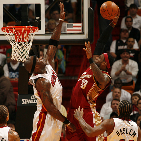 LeBron James  of the  Cleveland Cavaliers  goes  up strong to the  boards for the  dunk  over the  Miami  Heat's  Jermaine  O'Neal .