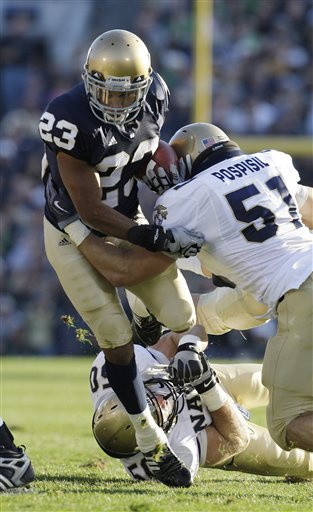 Notre Dame wide receiver Golden Tate (23) is tackled by Navy tackle Steve Spada (51) during the second quarter of an NCAA college football game in South Bend, Ind., Saturday, Nov. 7, 2009. (AP Photo/Darron Cummings)
