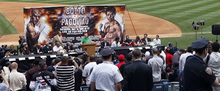 Fans and members of the  press  convene at  Yankees Stadium  at  a  press  conference  for the  upcoming   WBO  welterweight  title   bout  between   the title   holder  Miguel  Cotto  and   the challenger ,  Manny  Pacquiao  of the  Philippines .    At  the dais  is   Pacquiao's  trainer  Freddie Roach  ,  taking  questions  from the  press.     picture   appears  courtesy  of  ap/photo/ Will  Hart  ..........