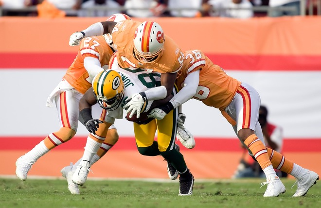 Buccaners'  defensive players  Torrie  Cox (27)  , Geno Hayes (54) and  Tanard Jackson (36)  set  about   tackling  Packers'  wide  receiver  James  Jones (89)   during  the  game .    picture  appears  courtesy  of  getty  images/  J  Meric ..........
