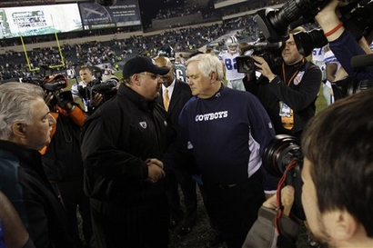 Eagles' head  coach  Andy  Reid  and  his  opposing   number   Wade Phillips of  the   Dallas Cowboys   meet  centerfield  after  the  game to  congratulate one another .