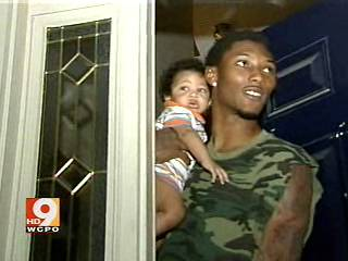 Bengals' wide receiver   Chris  Henry  , seen  here  with  one  of  his  three   young   children at  the   doorstep  of   his  home.   picture   comes courtesy of  wcpo.com Channel 9- Cincinnati ,Ohio .