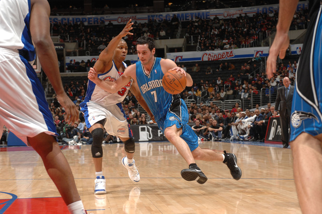 J.J. Redick (#7) of the Orlando Magic drives past Sebastian Telfair (#3) of the Los Angeles Clippers at Staples Center on December 8, 2009 in Los Angeles, California.   picture appears  courtesy of  NBAE/ getty images / Noah  Graham  .........