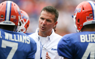 Meyer seen  here  speaking  to  a  number of  his  players  on  the  sidelines   during  a  college  game.  picture  appears  courtesy  of  ap/photo/  Brian  Joubert   .........