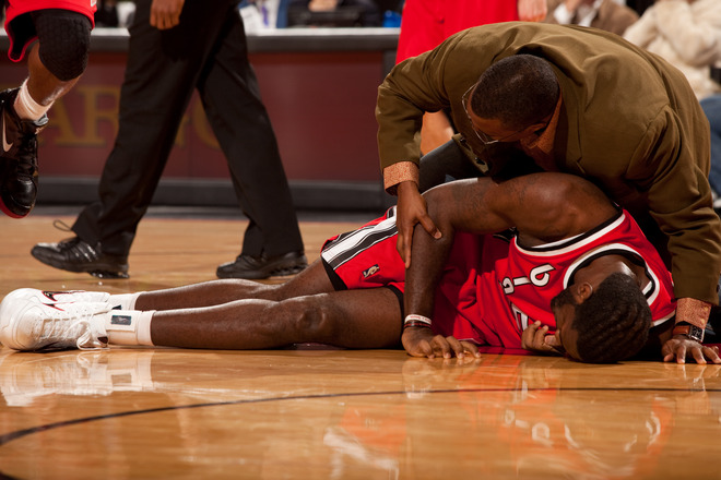 Greg Oden (52) of the Portland Trail Blazers lays with a left knee injury and is helped by Keith Jones the athletic trainer of the Houston Rockets during a game on December 5, 2009 at the Rose Garden Arena in Portland, Oregon.  picture appears courtesy  of  NBAE/Getty Images/ Cameron Browne  .......