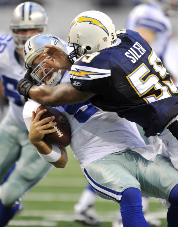 Tony  Romo (#9) of  the  Dallas Cowboys is  sacked  by the  Chargers'  linebacker  Brandon  Siler  (#55) during  the  game  played  at  the  Cowboys'  Texas Stadium  in  Arlington,  Texas.  The San Diego  Chargers  would  go  on  to  defeat the  Dallas Cowboys  20-17.    picture appears  courtesy of  ap/photo/  Michael  Thomas  ................