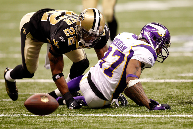 Bernard Berrian (#87) of the Minnesota Vikings fumbles the ball in the fourth quarter against Trscy Porter (#22) of the New Orleans Saints during the NFC Championship Game at the Louisiana Superdome on January 24, 2010 in New Orleans, Louisiana.  photo  appears  courtesy of Getty  Images/ Chris  Graythen  ..............