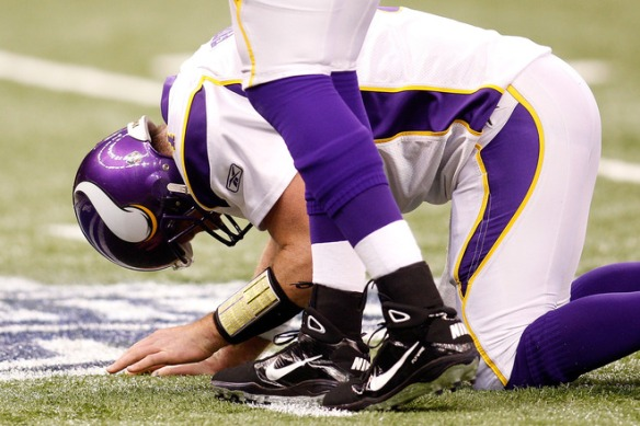 Quarterback Brett Favre (#4) of the Minnesota Vikings<strong> kneels on the turf in pain after he took a hard hit </strong> against the New Orleans Saints during the NFC Championship Game at the Louisiana Superdome on January 24, 2010 in New Orleans, Louisiana.  photo appears  courtesy  of Getty Images/  Chris  Graythen  ................