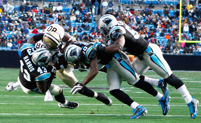 Charlotte, Nc,.  (R-L) Jon Beason (#52) , Charles Godfrey (#30) and Chris Harris (#43) of the Carolina Panthers tackle Darnell Dinkins (#80) of the New Orleans Saints in the second half of the game at Bank of America Stadium on January 3, 2010 in Charlotte, North Carolina.  picture appears courtesy of Getty Images / Scott Halleran  .......