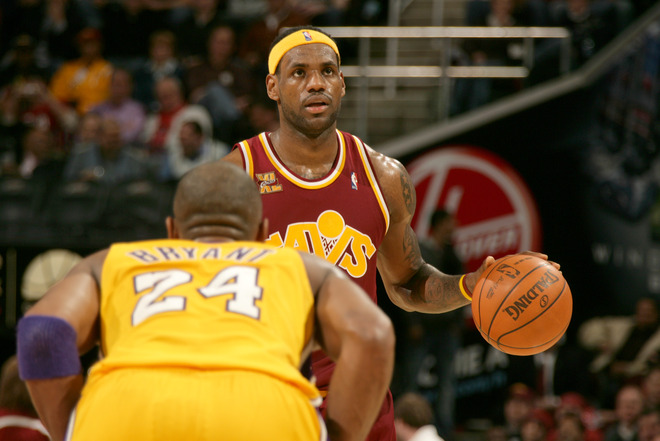 LeBron James (#23) of the Cleveland Cavaliers eyes the shot clock as he brings the ball down the court against Kobe Bryant (#24) of the Los Angeles Lakers on January 21, 2010.   photo appears  courtesy  of  NBAE/Getty Images/ David Liam .......