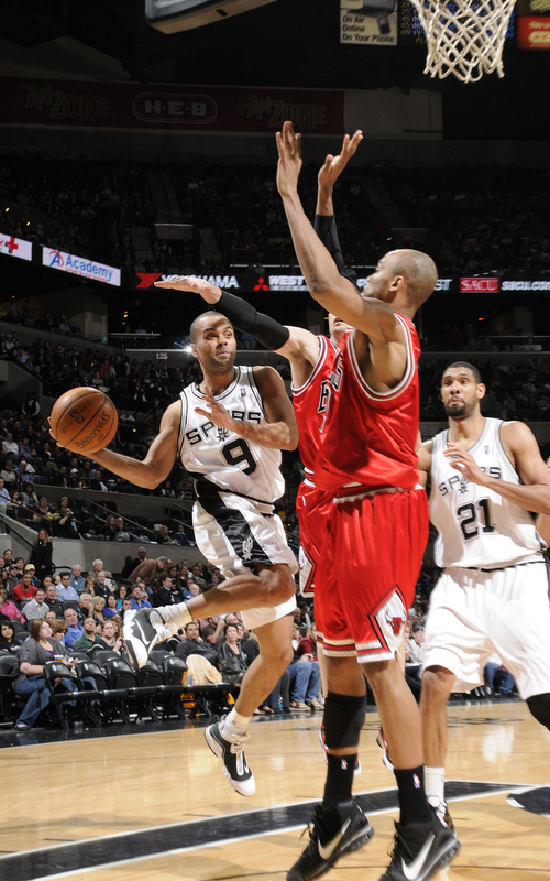 Tony Parker<strong> (#9)</strong> of the San Antonio Spurs jumps to pass over Taj Gibson <strong>(#22)</strong> of the Chicago Bulls on January 25, 2010 at the AT&T Center in San Antonio, Texas.
