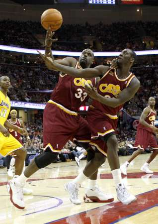 Cleveland Cavaliers' Shaquille O'Neal  (left) and J.J. Hickson try to control a rebound during the third quarter of their NBA basketball game against the Los Angeles Lakers in Cleveland January 21, 2010.  photo appears  courtesy  of Reuters /Aaron Josefczyk ...............