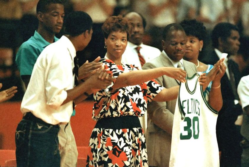 Joined by her husband James, right, and son Jay, in green shirt, Lonise Bias holds up a jersey presented by Red Auerbach on June 24, 1986.