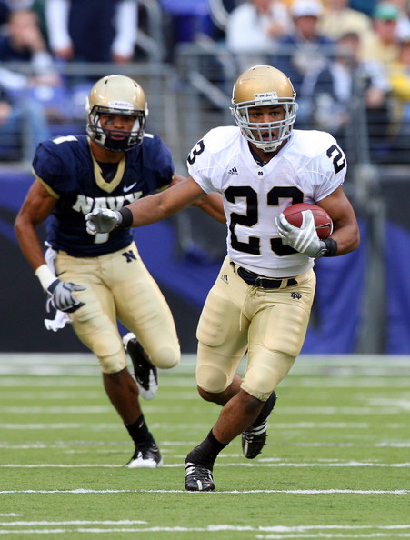 Golden Tate #23 of the Notre Dame Fighting Irish runs the ball past Blake Carter #1 of the Navy Midshipmen on November 15, 2008 at M&T Bank Stadium in Baltimore, Maryland. Notre Dame defeated Navy 27-21.