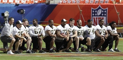 A group of New Orleans Saints players pose on the Super Bowl logo at the 50-yard line for a souvenir photograph during football practice at Sun Life Stadium on Saturday, Feb. 6, 2010 in Miami. The Saints play the Indianapolis Colts in the NFL football Super Bowl XLIV on Sunday. photo  appears  courtesy of Associated Press /  Mark  Humphrey  ......