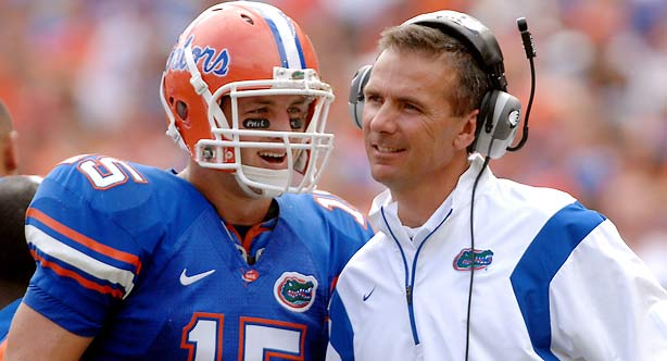 Gatots'  player  Tim  Tebow (15) and   his  coach    Urban  Meyer   discuss  their options  during  a  game.   photo   appears   courtesy  of   Getty Images/ Chris   Dickson ...................