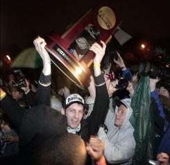 Butler's Nick Rodgers hold up the West Regional trophy as the team returned home to Indianapolis amid a throng of fans after earning a spot in the Final Four with a victory over Kansas State Saturday.