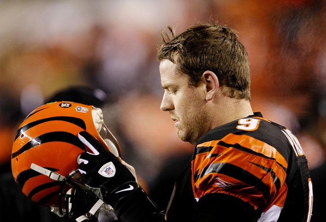 Quarterback Carson Palmer #9 of the Cincinnati Bengals looks down at his helmet late in the fourth quarter against the New York Jets during the 2010 AFC wild-card playoff game at Paul Brown Stadium on January 9, 2010 in Cincinnati, Ohio. photo appears  courtesy of  Getty  Images/ Jonathan Daniel ....