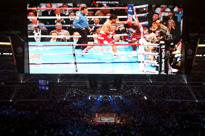 Manny Pacquiao of the Philippines throws a left to the head of Joshua Clottey of Ghana during the WBO welterweight title fight at Cowboys Stadium on March 13, 2010 in Arlington, Texas.  The  view  from the  giant  jumbotron  as   viewed  by  the  fans  in attendance. photo appears courtesy of  Getty  Images/  Jed  Jacobsohn  ..........