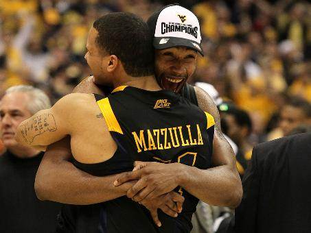 West Virginia's Da'Sean Butler and Joe Mazzulla hug after the game. Butler scored 18 points and Mazulla pitched in a career-high 17 to help West Virginia hold off the Wildcats.
