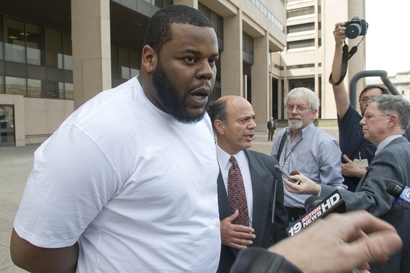 Cleveland Browns nose tackle Shaun Rogers and his lawyer Patrick D'Angelo, center, talk to reporters after leaving Cleveland Police Headquarters where Rogers was charged with one felony count of carrying a concealed weapon on Friday, April 2, 2010, in Cleveland, Ohio. Rogers was arrested at Cleveland Hopkins International airport on Thursday after he tried to take a loaded handgun through airport security. photo appears courtesy of Associated Press/ Jason Miller .....