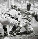 Jackie Robinson seen stealing home plate in game played for the Brooklyn Dodgers . The fabled and legendary Robinson became the first person of color to play the game professionally in the game of baseball. His integration into the sport would open the floodgates and the opportunities for others across all racial barriers to compete in competitive team sports. @ copyrighted material ........... Marcus Childs ..........