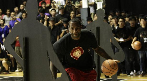 The Cleveland Cavaliers' LeBron James dribbles around cutout statues, demonstrating a drill during a promotional event in Beijing. James is in China on a worldwide tour to promote a new Nike shoe and to offer grassroots basketball activities. The NBA All-Star is also on a promotional tour for the documentary film More Than a Game, which traces James' journey with his high school teammates on and off the court. Reuters / Jason Lee ........