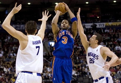 New York Knicks' Tracy McGready, centre, shoots despite pressure from Toronto Raptors' Andrea Bargani, left, and Hedo Turkoglu, right, during first half NBA action in Toronto on Friday March 5, 2010. A person familiar with the negotiations tells The Associated Press that Tracy McGrady has agreed to terms of a one-year contract with the Detroit Pistons. The person, who spoke Tuesday, Aug. 10, 2010, on the condition of anonymity because the deal hasn't been announced, says McGrady will play for $1.3 million this season.
