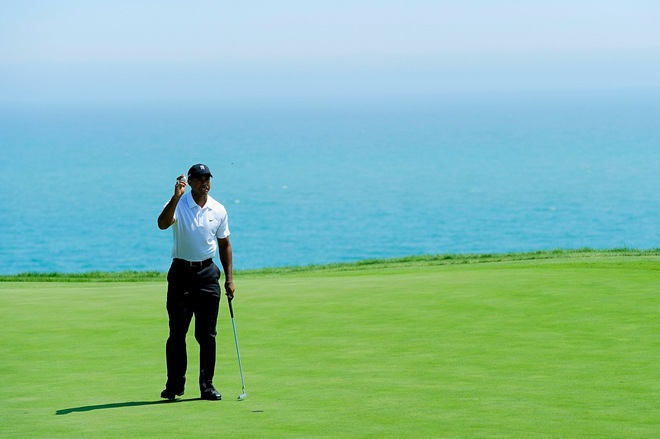 Tiger Woods waves to fans after making par on the 12th hole during the first round of the 92nd PGA Championship on the Straits Course at Whistling Straits on August 12, 2010 in Kohler, Wisconsin. Photo by Stuart Franklin/Getty Images .....