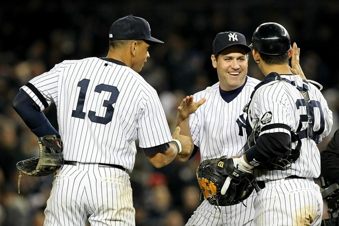 Alex Rodriguez (13), Lance Berkman (17) and Jorge Posada (20) of the New York Yankees celebrate after the Yankees won 7-2 against the Texas Rangers in Game Five of the ALCS during the 2010 MLB Playoffs at Yankee Stadium on October 20, 2010 in the Bronx borough of New York City. Photo by Al Bello/Getty Images) .....