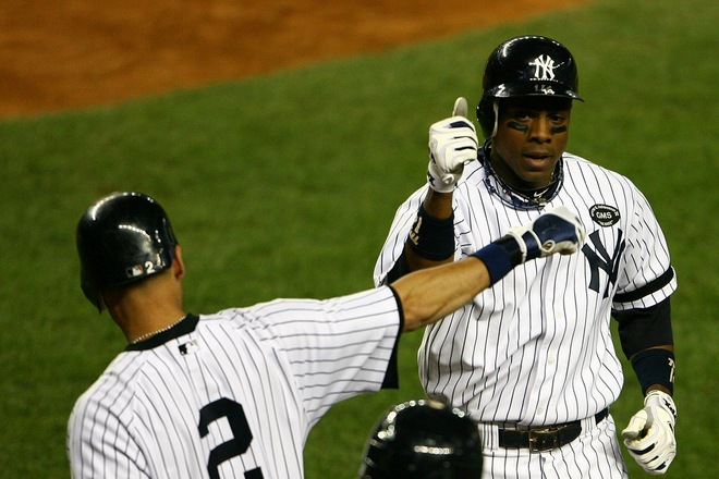 Curtis Granderson (14) of the New York Yankees celebrates with Derek Jeter (2) after Granderson hit a solo home run in the bottom of the eighth inning against the Texas Rangers in Game Five of the ALCS during the 2010 MLB Playoffs at Yankee Stadium on October 20, 2010 in the Bronx borough of New York City. Photo by Andrew Burton/Getty Images .....