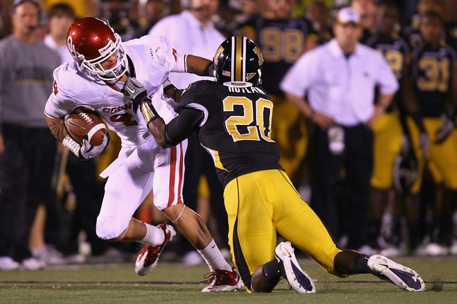 Kenny Stills (4) of the Oklahoma Sooners is tackled by Kevin Rutland (20) of the Missouri Tigers at Faurot Field/Memorial Stadium on October 23, 2010 in Columbia, Missouri. The Tigers beat the Sooners 36-27 . Photo by Dilip Vishwanat/Getty Images ....