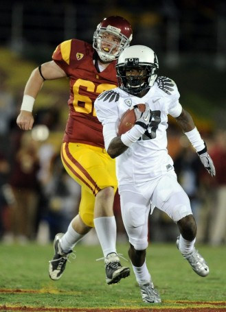 Cliff Harris (13) of the Oregon Ducks runs past Chris Pousson (62) of the USC Trojans during the second quarter at Los Angeles Memorial Coliseum on October 30, 2010 in Los Angeles, California. Photo by Harry How/Getty Images ........,/b>