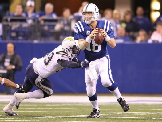 Peyton Manning (18) of the Indianapolis Colts looks to throw a pass while pursued by Kevin Burnett (99) of the San Diego Chargers during the NFL game at Lucas Oil Stadium on November 28, 2010 in Indianapolis, Indiana. The Chargers won 36-14 . Photo by Andy Lyons/Getty Images