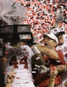Oklahoma coach Bob Stoops reaches over to touch the trophy following their 23-20 win in the NCAA Big 12 college football championship game against Nebraska Saturday, Dec. 4, 2010, in Arlington, Texas. AP Photo/Tony Gutierrez .......