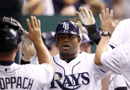 This July 27, 2010, file photo shows Tampa Bay Rays' Carl Crawford being congratulated after scoring in the sixth inning of the Rays' 3-2 victory over the Detroit Tigers in a baseball game in St. Petersburg, Fla. Crawford has reached a preliminary agreement with the Boston Red Sox on a $142 million, seven-year contract, a person familiar with the negotiations told The Associated Press. The agreement is subject to Crawford passing a physical, the person said Wednesday night, Dec. 8, 2010. AP Photo/Mike Carlson ........